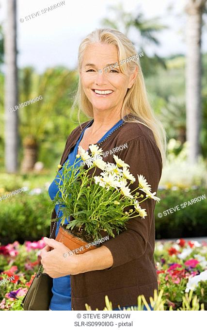 Woman with plant in pot at garden centre