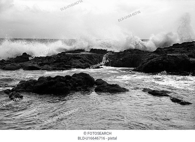 Landscape shot of waves crashing into rocky Hawaii coast