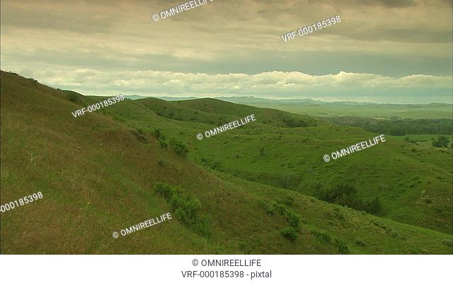 Green countryside hills with clouds behind