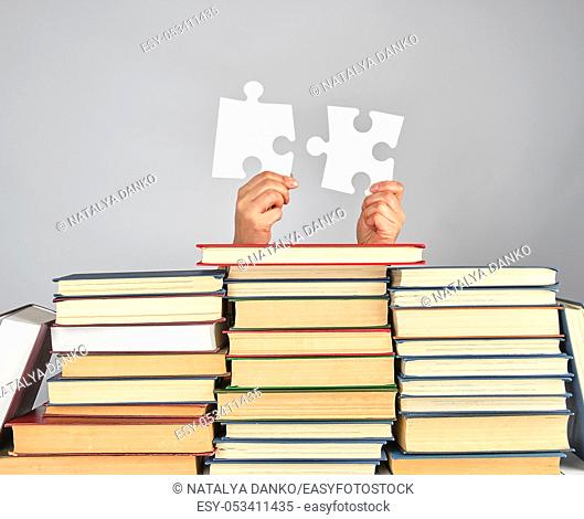 female hands holding big white puzzles over a stack of books, gray background
