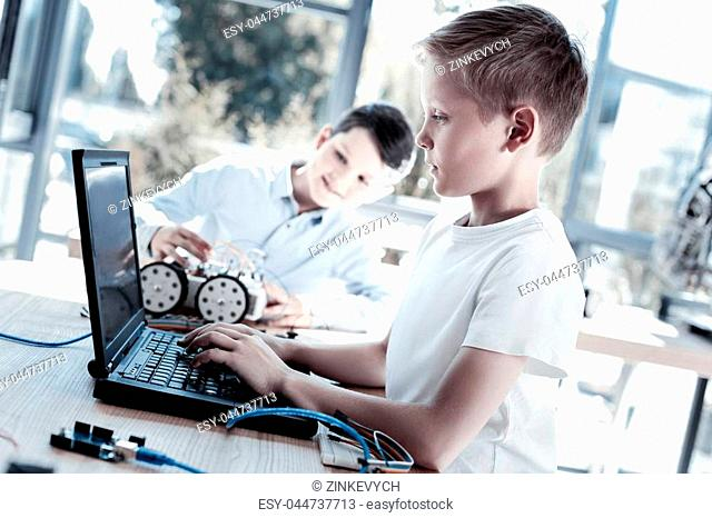 Innovative generation. Side view on a completely absorbed in the process youngster working on a laptop and programming after designing a new robotic machine...