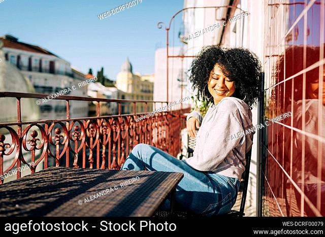 Happy young woman with curly hair sitting on balcony enjoying the sunshine