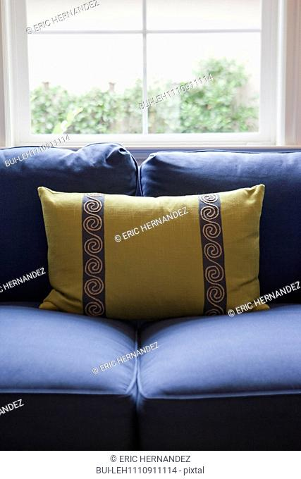 Close-up of a cushion on blue couch against window in the living room at home