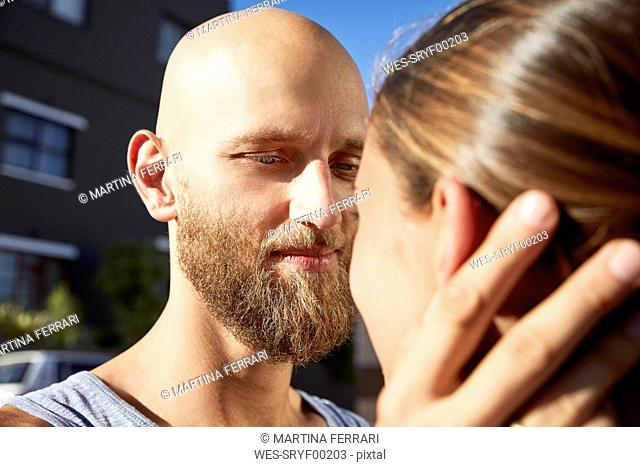 Portrait of bald young man face to face with his girlfriend