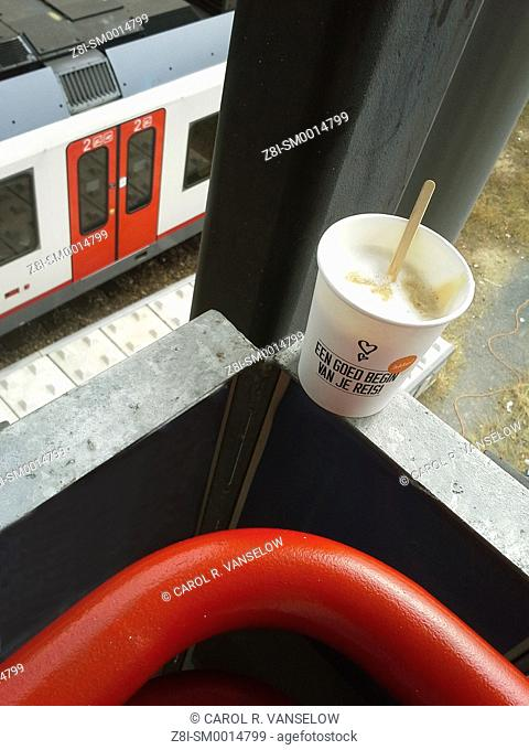 Cup of cappuccino to go sitting on railing, platform overlooking the train platform in Heerlen train station. On cup is written in Dutch 'a good way to begin...