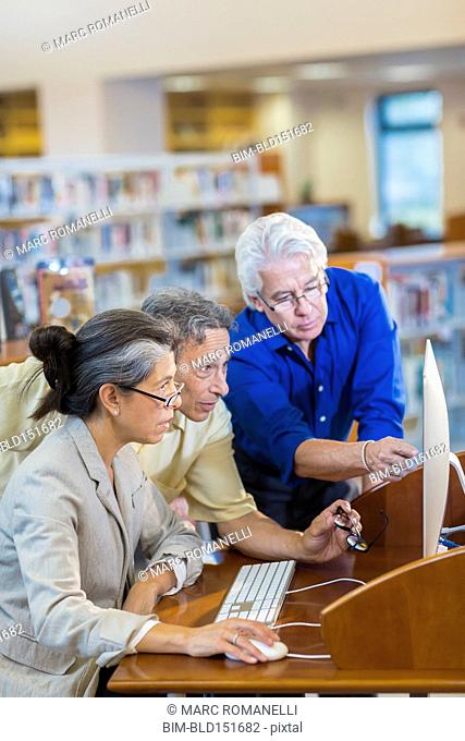 Teacher helping adult students use computer in library