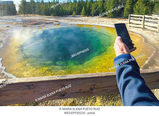 USA, Wyoming, Yellowstone National Park, man taking photos at Morning Glory Pool