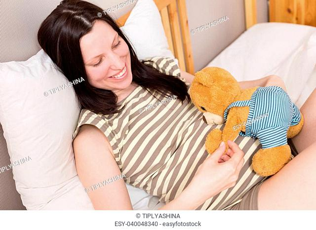 Pregnant woman relaxing at home on the bed