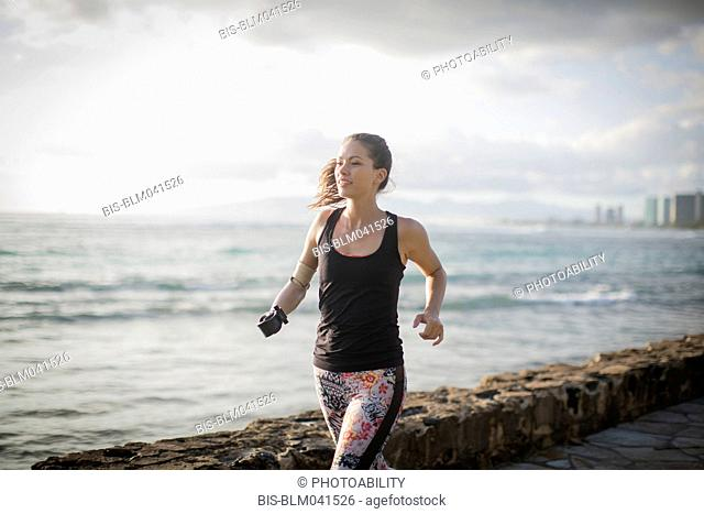 Mixed race amputee athlete jogging on urban waterfront