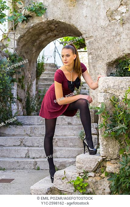 Beautiful young woman posing in Mediterranean old-town