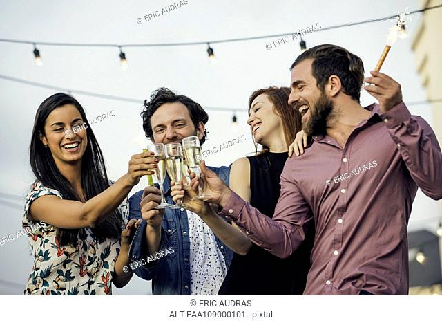 Friends clinking champagne glasses outdoors