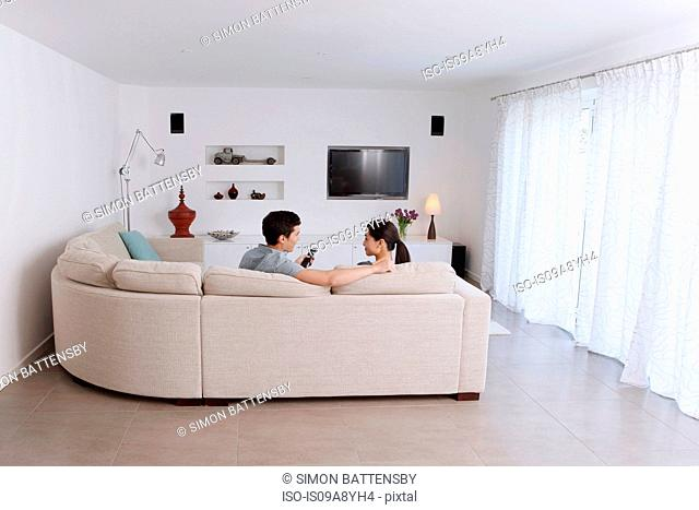 Husband and wife relaxing on corner sofa in living room