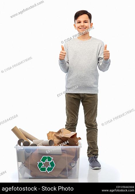 smiling boy sorting paper waste showing thumbs up