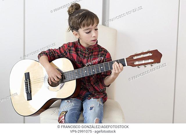 10 year old girl playing the Spanish guitar. Horizontal shot