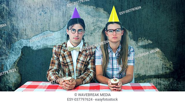 Composite image of unsmiling geeky hipsters celebrating birthday
