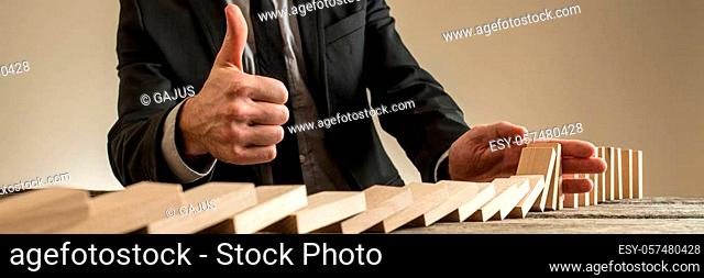 Wide view image of businessman showing thumbs up sign as he stops the dominos from falling with his hand in a conceptual image