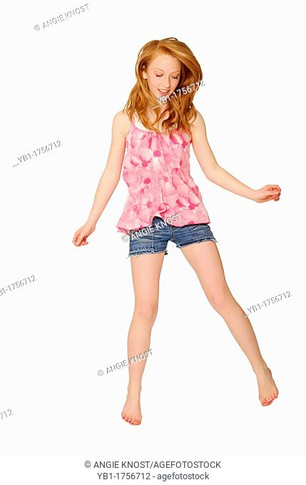 Pretty fourteen year old girl wearing pink flowered shirt and cutoff bluejean shorts, jumping or bouncing  Her red hair looks healthy and bouncing