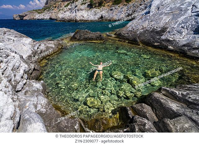 A man relaxing on the water of a natural pool with sea water. Trachila village, Messenia, Greece