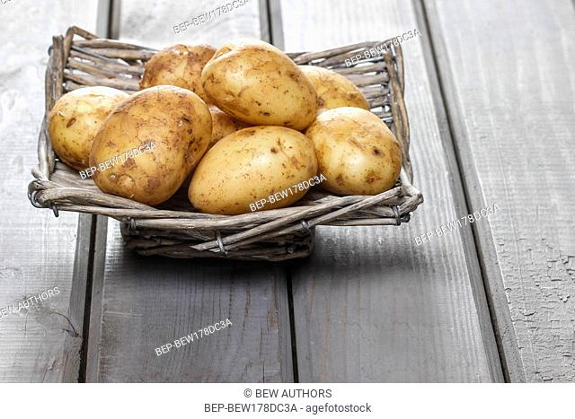 Basket of potatoes on grey wooden table