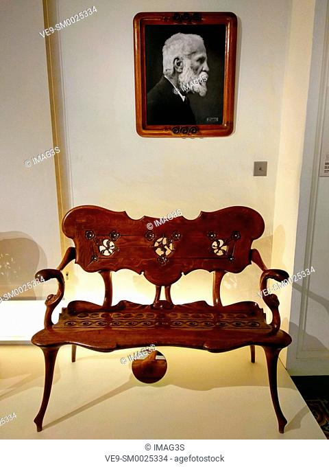 A bench designed by Antonio Gaudí and his portrait inside the Gaudi House Museum in Park Guell, Barcelona, Spain