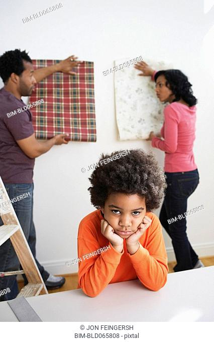 Bored African boy waiting while parents choose wallpaper