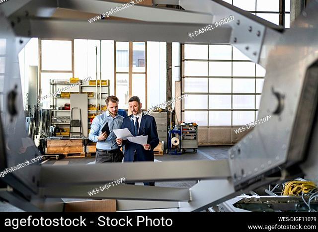 Two businessmen having a meeting in a factory