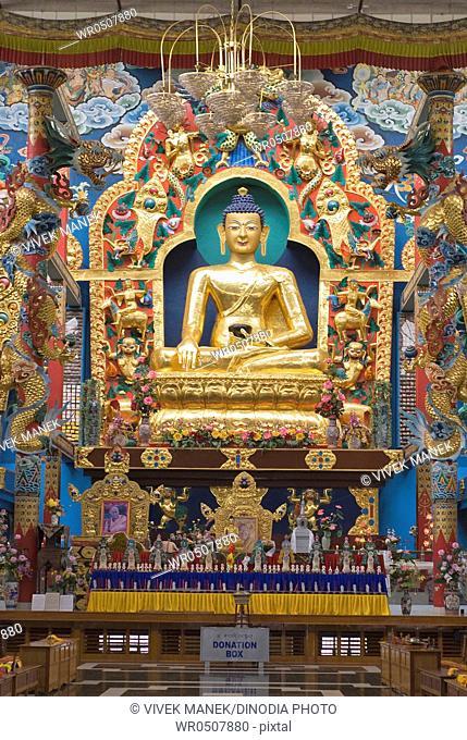Golden Buddha statue in Namdroling monastery Palyul Nyingmapa Buddhist Centre Byalakuppe , Mysore District , Karnataka , India