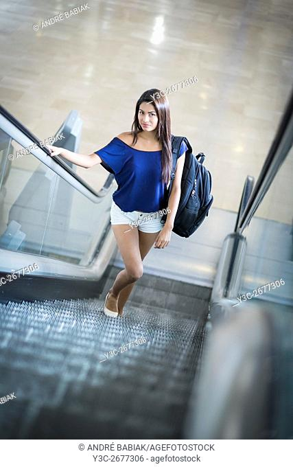 Young beautiful woman with backpack going up on an escalator