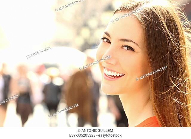 Woman face smile with perfect teeth and smooth skin looking you on the street