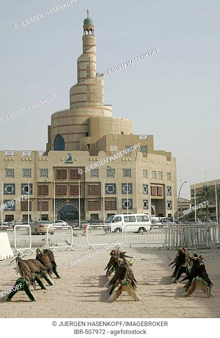 Qatar, Doha, the big tower of the FANAR (Qatar Islamic Cultural Center) building, Arabian architecture, in the foreground falcons are sitting in front of a...