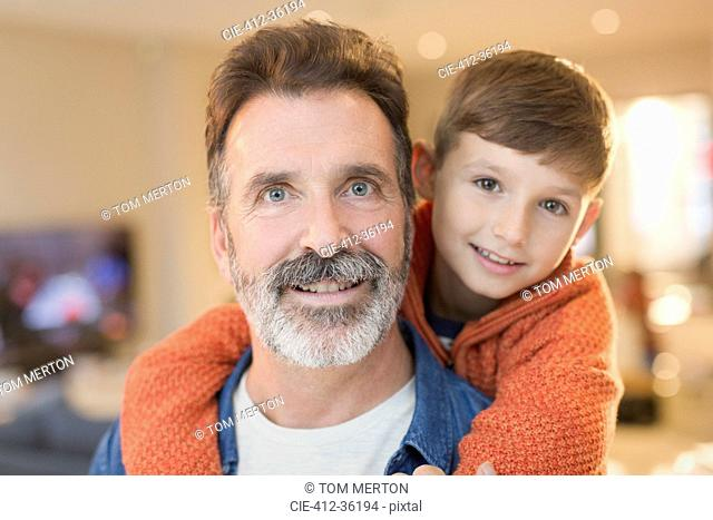 Close up portrait smiling father and son hugging