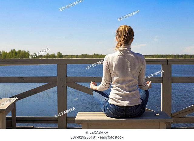 Young woman practicing yoga in front of lake. Yoga and meditation concept