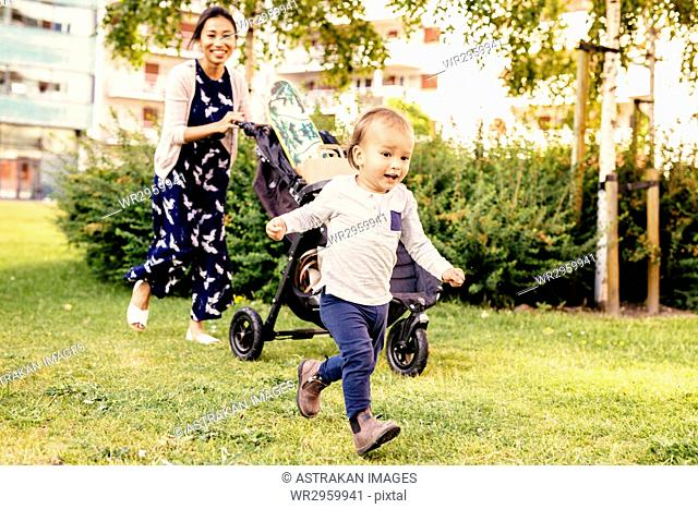 Boy (2-3) running on grass and mother walking with baby stroller in background
