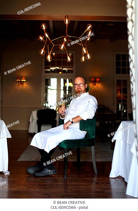 Portrait of chef with glass of wine in luxury restaurant