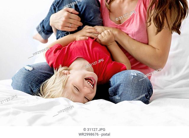 Woman sitting on a bed, playing with a blond boy wearing red T-shirt