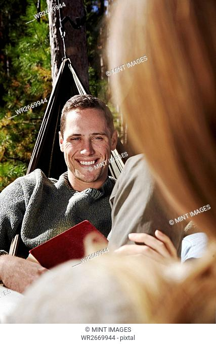 Two people sitting in hammocks outdoors. A man smiling at a companion