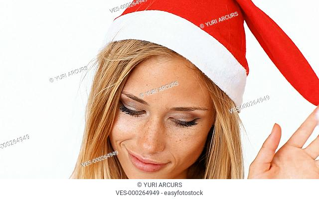 A cute young woman showing excited facial expressions wearing a red santa hat, isolated on white