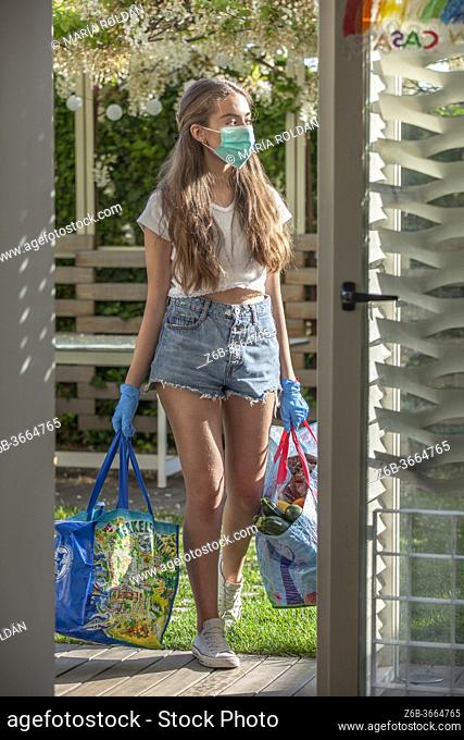 young girl coming in home from market, she wears mask and gloves