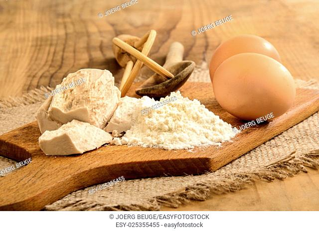 fresh yeast, flour and eggs, ingredients to bake a cake on wooden board