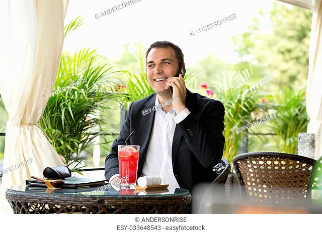 Young businessman talking on a cell phone and drinking a cocktail sitting in a summer restaurant