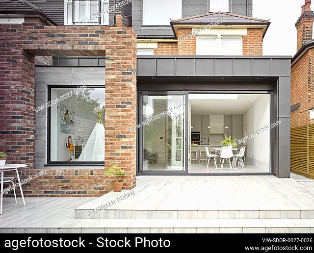 View from garden towards rear extension with open sliding doors. Hillcrest Drive, London, United Kingdom. Architect: Selecky Parsons, 2020