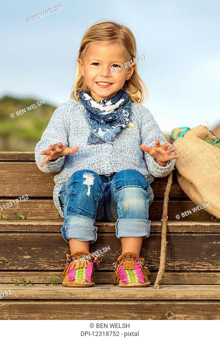 Portrait of a young girl sitting on wooden steps; Tarifa, Cadiz, Andalusia, Spain