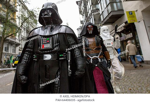Members of a local 'Star Wars' fan club dressed as characters from the Star Wars movies Darth Vader (l-r), Darth Revan and Snowtrooper walk through the streets...