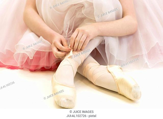 A ballerina sitting on the floor tying her ballet shoes