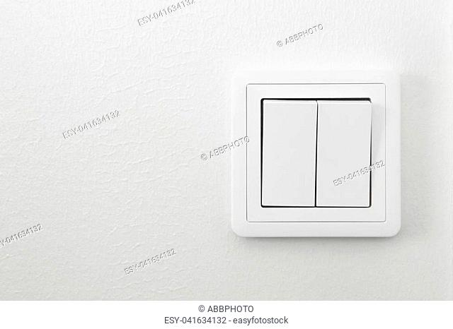 Light switch on a white textured wall. Home indoor detail