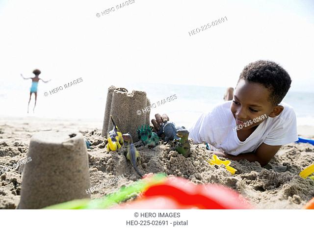 Smiling boy playing toys and sandcastle on beach