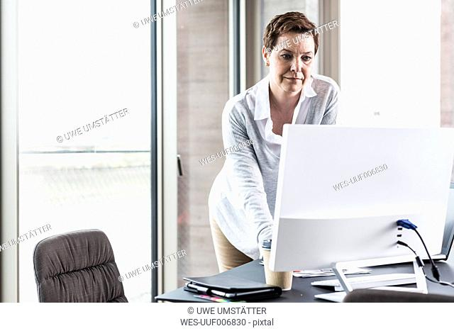 Businesswoman looking at computer monitor in office