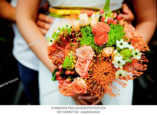 Wedding bouquet held by bride and groom. Shallow depth of field