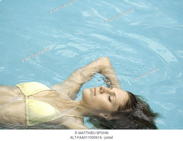 Woman floating on back in pool