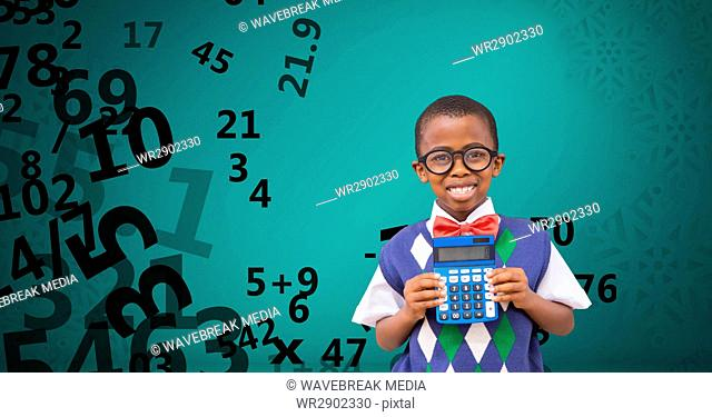 Happy school boy holding calculator against flying numbers